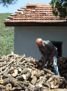 Griechischer Rentner beim hacken von Feuerholz